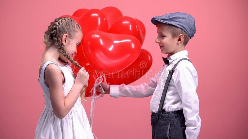 Garçon dans l'amour donnant à fille mignonne les ballons en forme de coeur, surprise de jour de valentines photographie stock