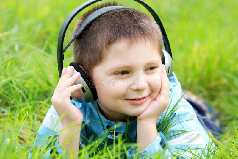 Garçon dans l'herbe appréciant la musique images stock