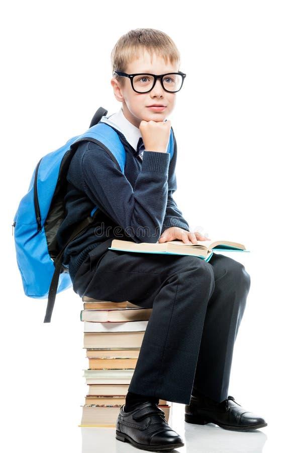 Garçon dans l'uniforme scolaire avec des livres sur un fond blanc photo stock