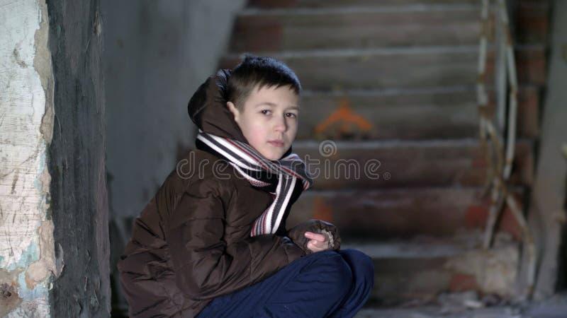 Garçon dans la dépression, regardant la caméra, se cachant du froid dans une vieille maison délabrée images libres de droits