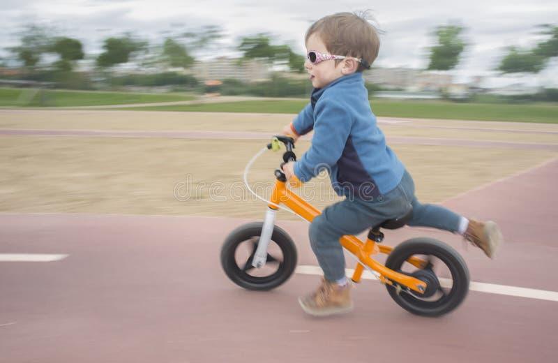 Garçon dans la veste bleue montant rapidement un vélo orange d'équilibre ou un Bi couru image stock