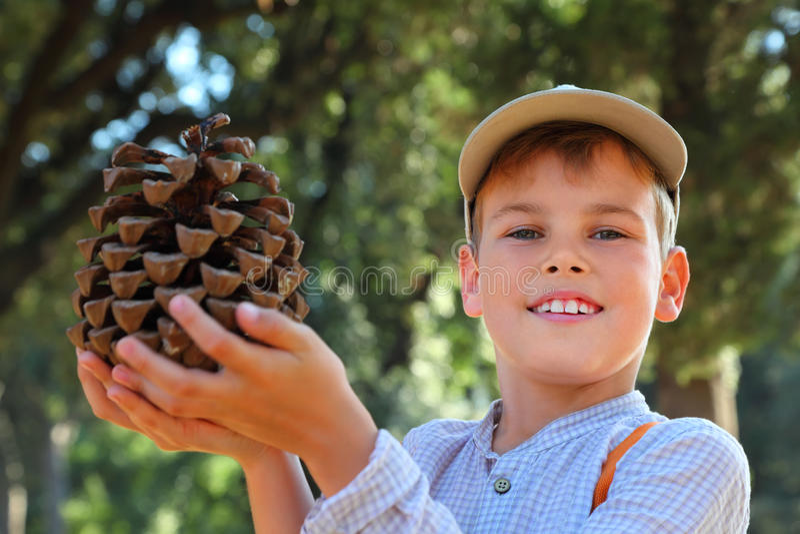 Garçon dans le capuchon et la chemise checkered retenant le grand cône photographie stock