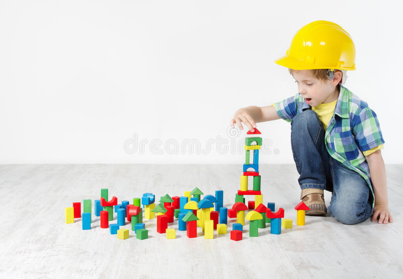 Garçon dans le casque antichoc jouant avec des blocs photographie stock