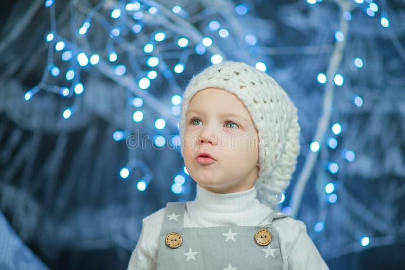 Garçon dans le chapeau blanc sur un fond des lumières bleues photo stock