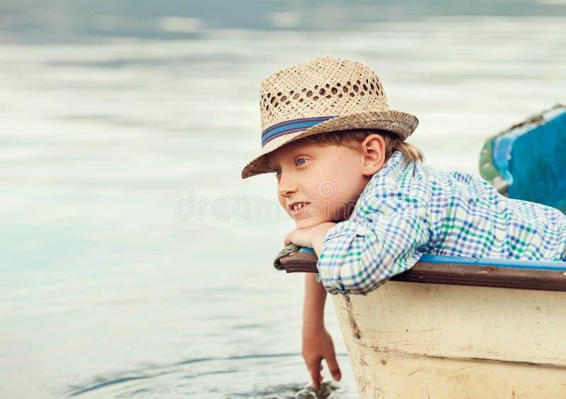 Garçon dans le chapeau de paille se situant dans le vieux bateau photos stock