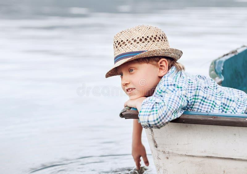Garçon dans le chapeau de paille se situant dans le vieux bateau photographie stock