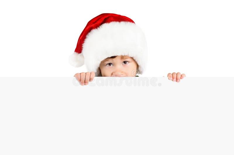 Garçon dans le chapeau de Santa avec le panneau blanc images libres de droits