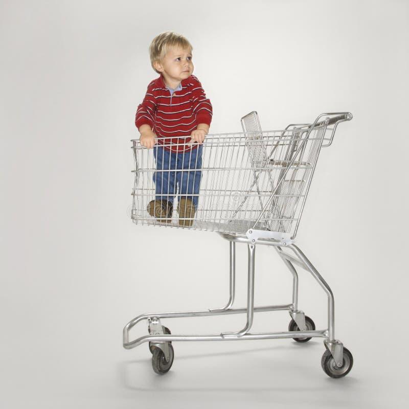 Garçon dans le chariot vide. photographie stock