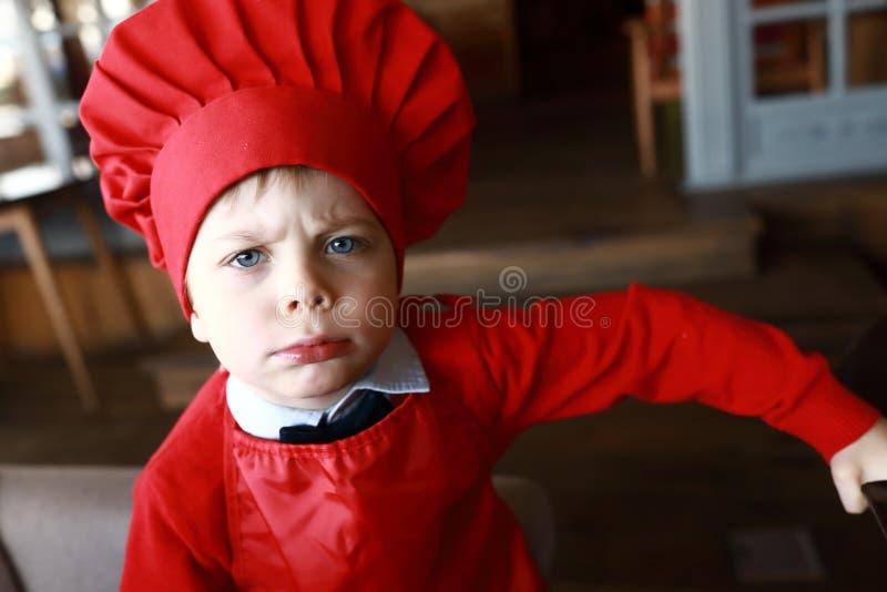 Garçon dans le cuisinier rouge de chapeau image stock