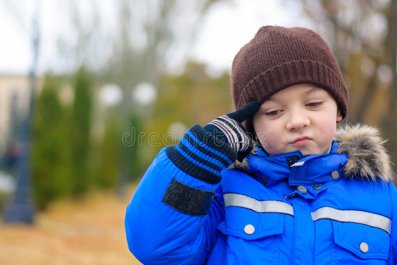 Garçon dans le doigt réfléchi de veste bleue à diriger image libre de droits
