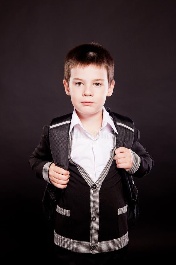 Garçon dans le dresscode officiel avec le sac à dos photo stock