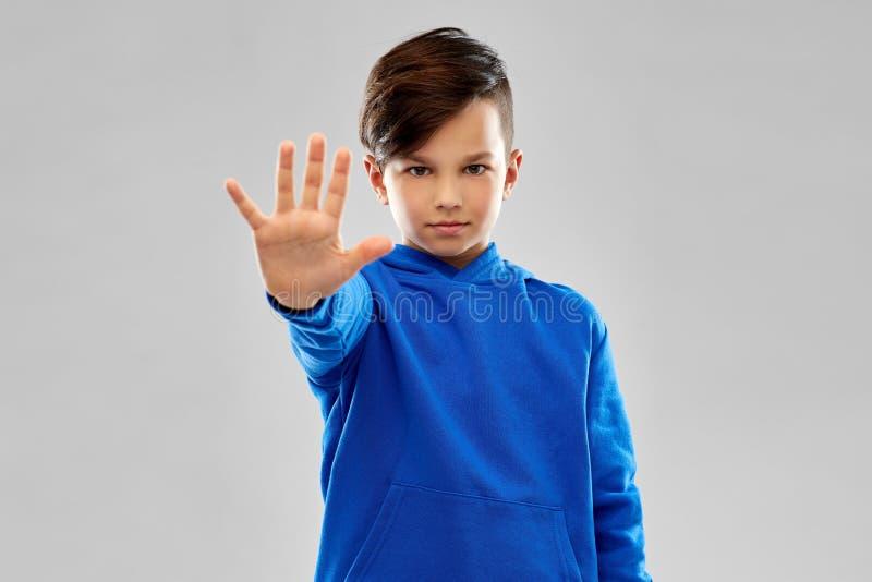 Garçon dans le hoodie bleu faisant arrêter le geste images stock