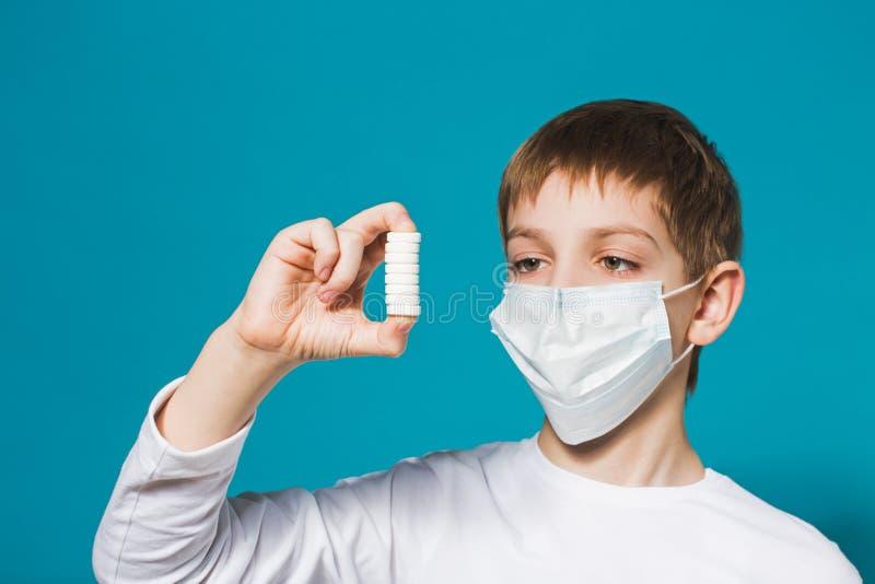 Garçon dans le masque de protection regardant des pilules photo stock