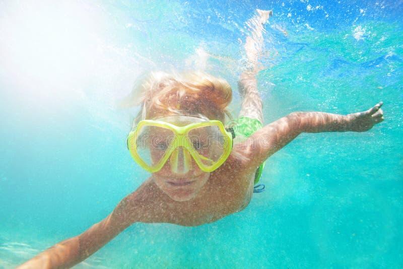 Garçon dans le masque de scaphandre nageant sous l'eau photo libre de droits