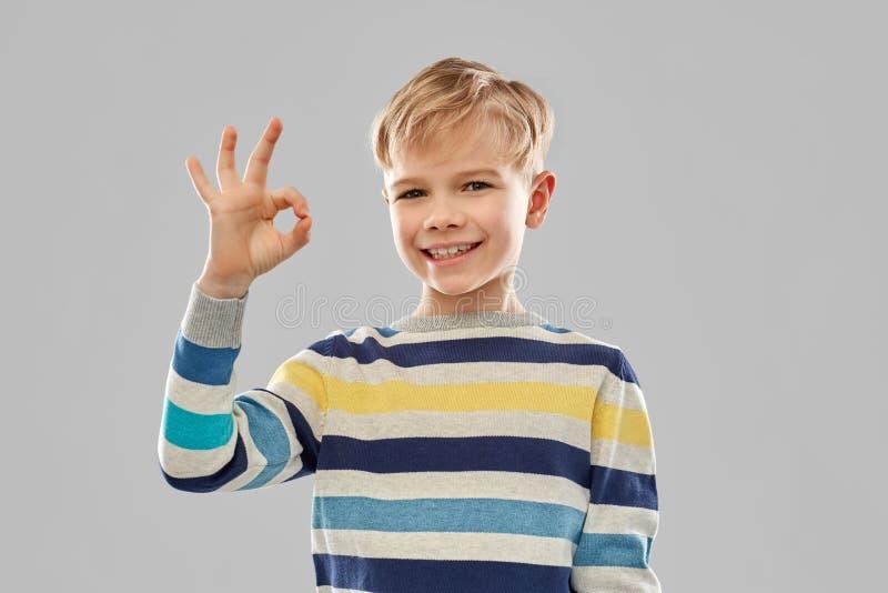 Garçon dans le signe correct de main d'apparence rayée de pull image libre de droits
