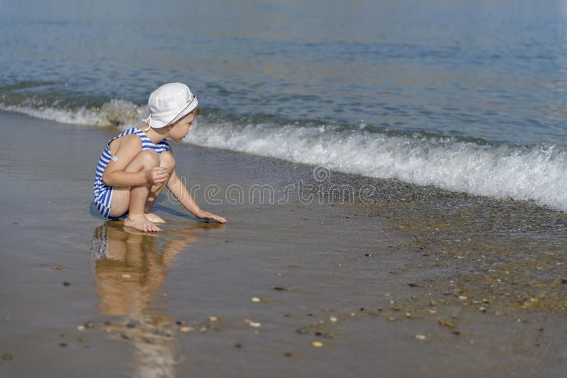 Garçon dans le T-shirt rayé sur la plage photographie stock