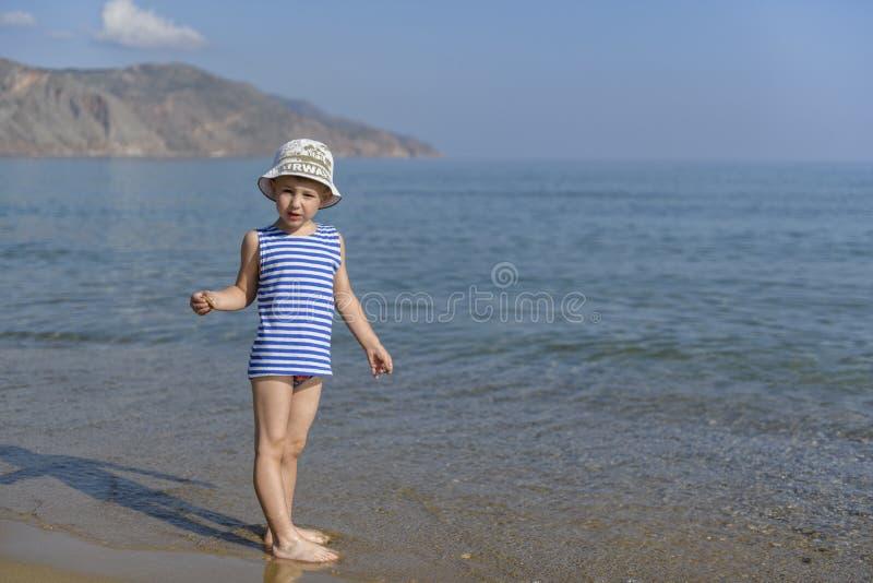 Garçon dans le T-shirt rayé sur la plage image stock