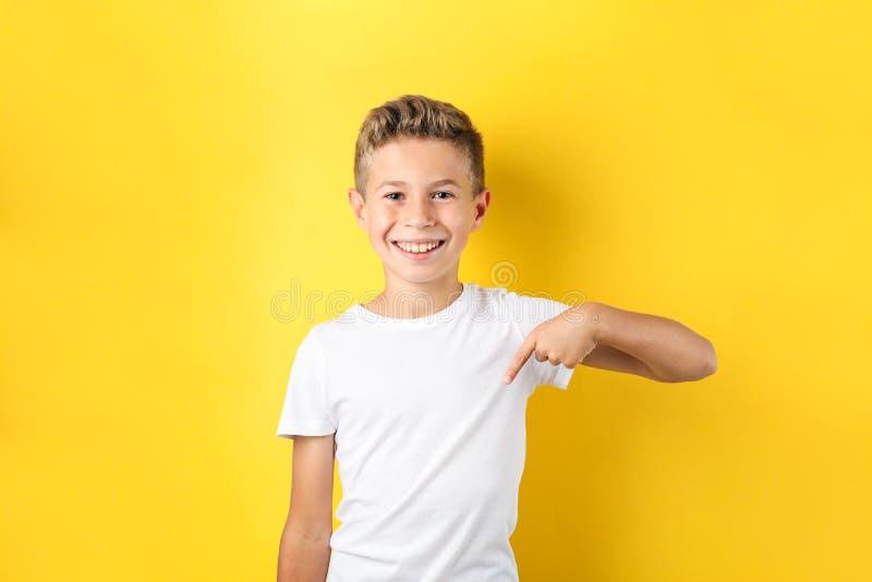 Garçon dans le T-shirt sur le fond jaune photographie stock