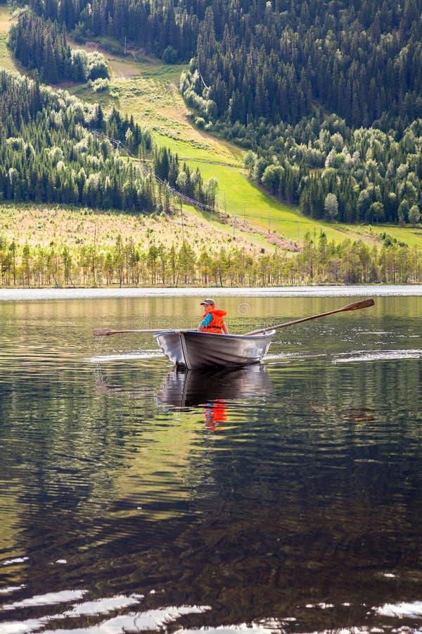 Garçon dans un bateau à rames sur un lac de montagne photo libre de droits