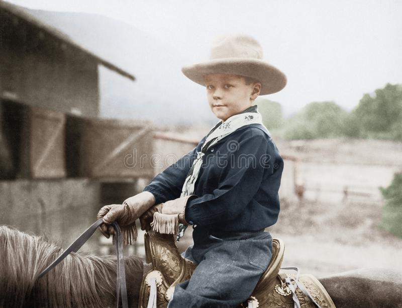 Garçon dans un chapeau de cowboy sur un cheval (toutes les personnes représentées ne sont pas plus long vivantes et aucun domaine photographie stock libre de droits