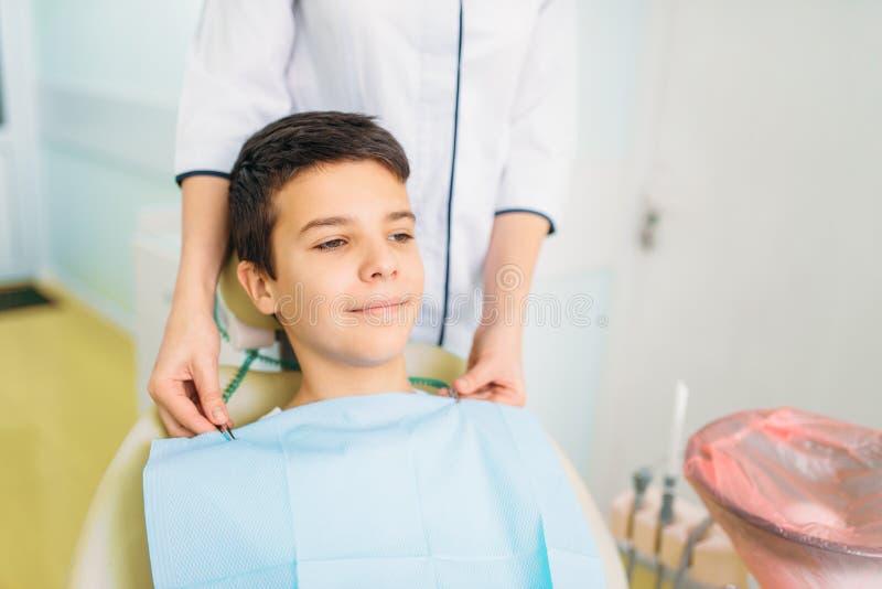 Garçon dans une chaise dentaire, art dentaire pédiatrique images libres de droits