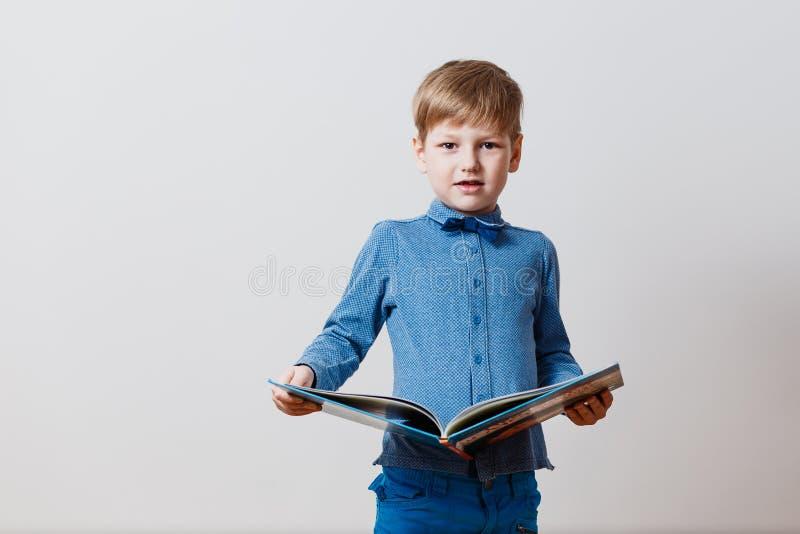 Garçon dans une chemise bleue avec un grand livre dans des ses mains photographie stock libre de droits