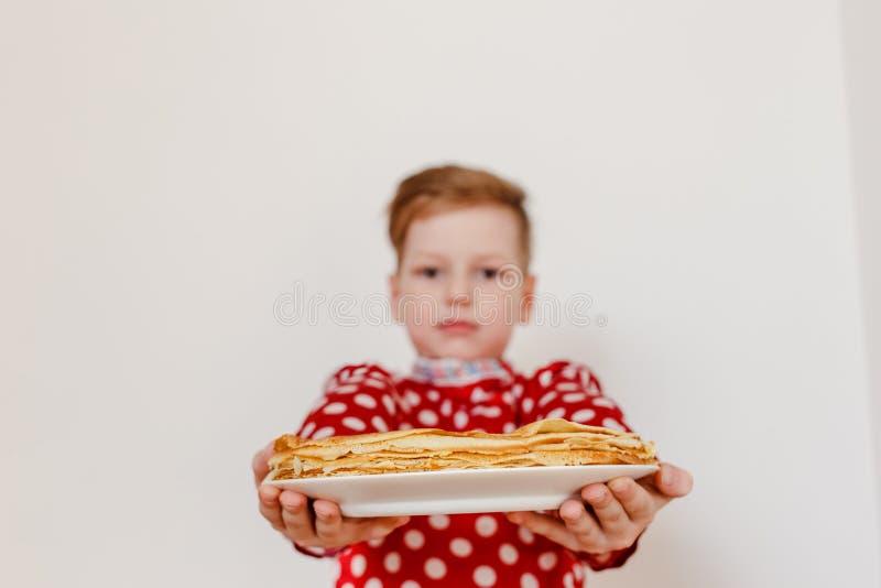 Garçon dans une chemise rouge tenant un plat avec des crêpes Crêpes dans le premier plan Les vacances de Maslenitsa photos stock