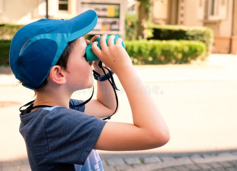 garçon de 8 ans regardant par des jumelles images libres de droits