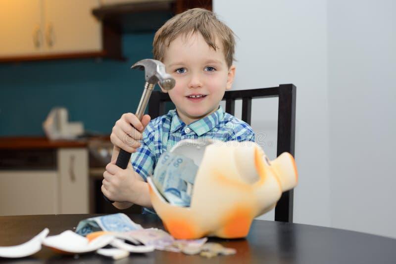 garçon de 4 ans satisfait de casser la tirelire photo libre de droits