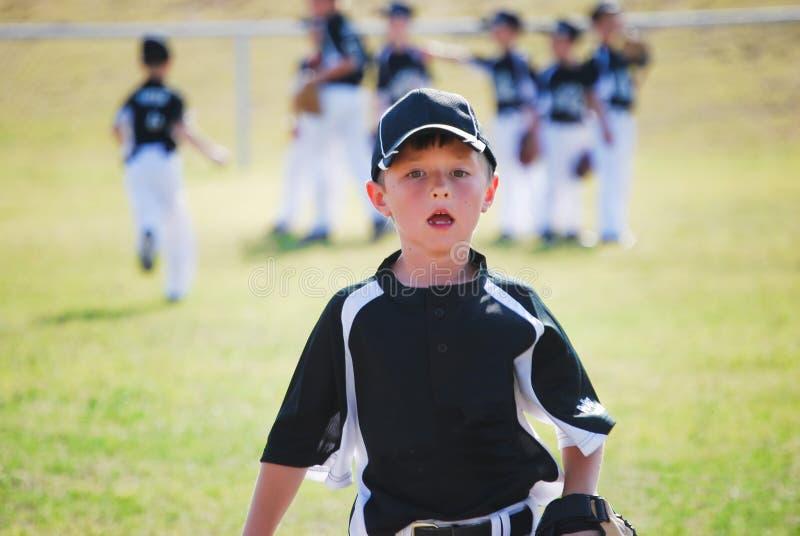 Garçon de base-ball d'équipe de minimes courant sur le champ photo stock