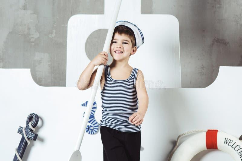 Garçon de cabine jouant avec la palette devant le bateau stylisé images libres de droits