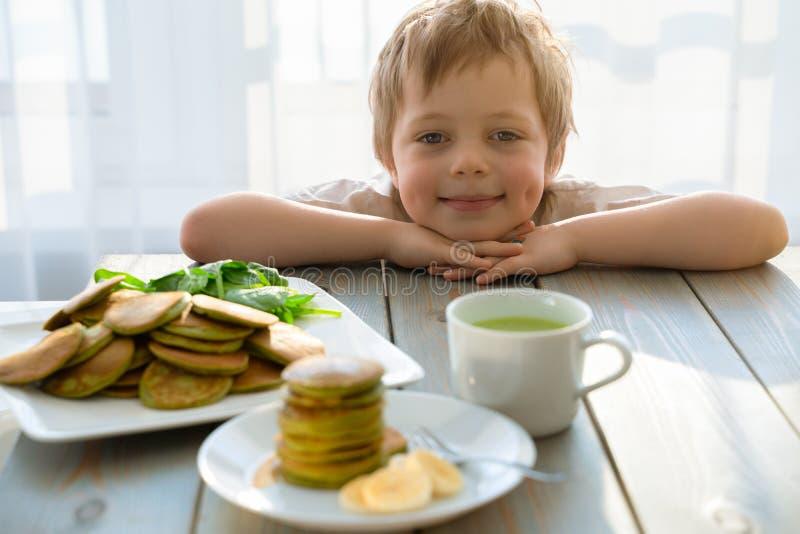 Garçon de cinq ans mignon avec la pile de crêpes d'épinards photo stock
