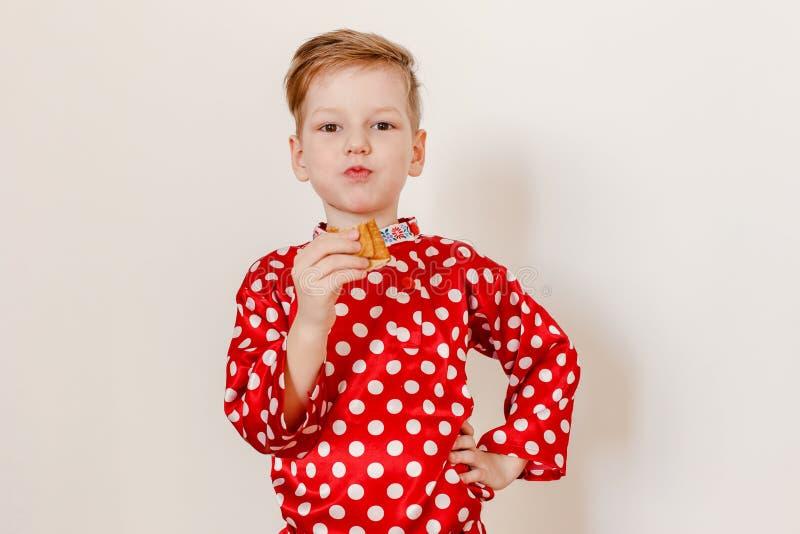 Garçon de cinq ans russe dans la chemise rouge dans le pois mangeant une crêpe sur un fond blanc photographie stock libre de droits