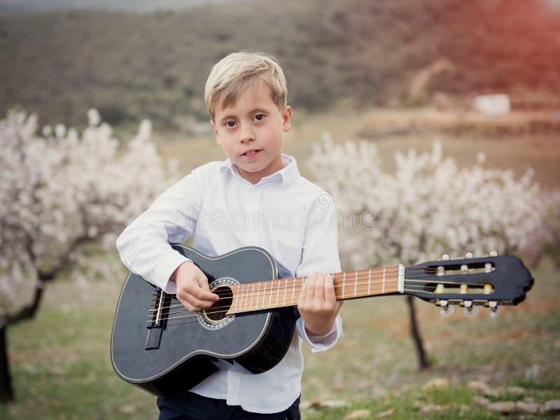 Garçon de Cuacasian avec la guitare en parc dehors photographie stock