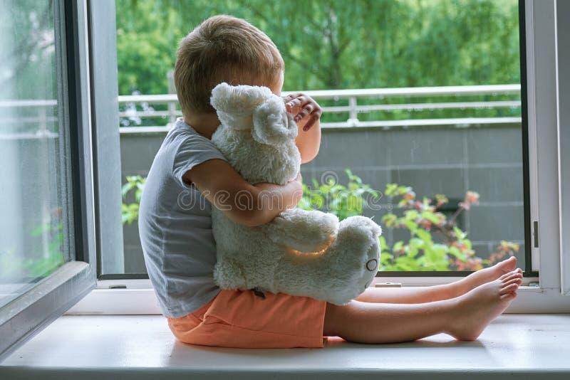 Garçon de deux ans se reposant par la fenêtre et les étreintes un lapin de jouet temps pluvieux, papa de attente à venir à la mai image libre de droits