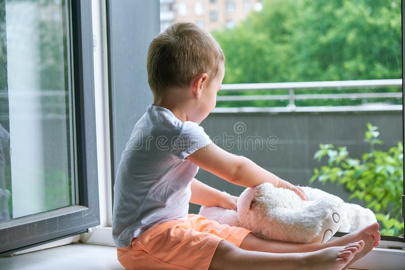 Garçon de deux ans se reposant par la fenêtre et les étreintes un lapin de jouet temps pluvieux, papa de attente à venir à la mai photo libre de droits