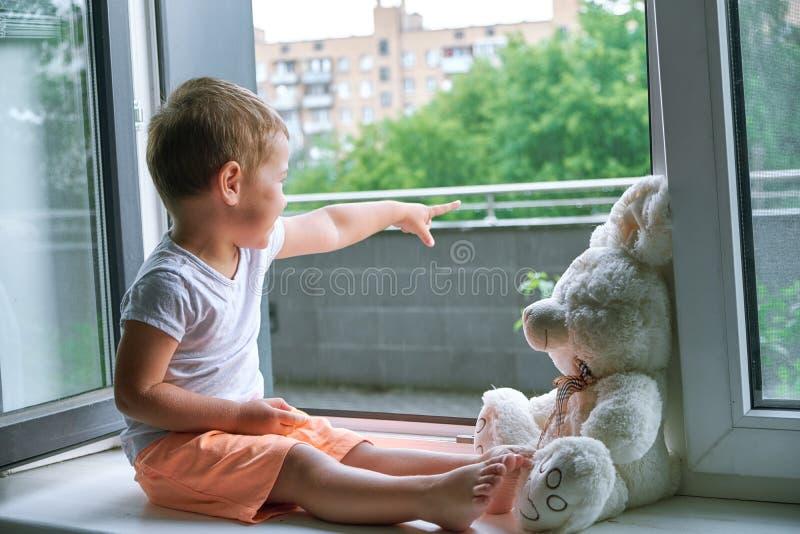 Garçon de deux ans se reposant par la fenêtre et les étreintes un lapin de jouet temps pluvieux, papa de attente à venir à la mai photographie stock