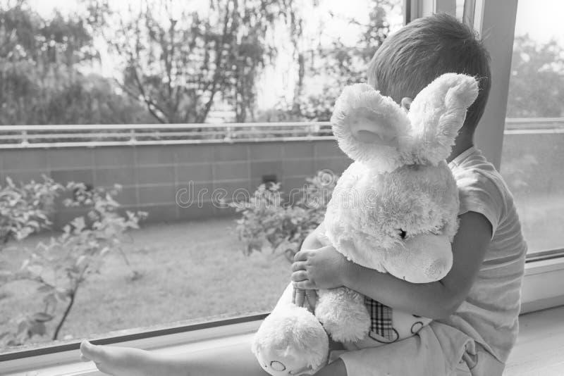 Garçon de deux ans se reposant par la fenêtre et les étreintes un lapin de jouet temps pluvieux, papa de attente à venir à la mai photos stock