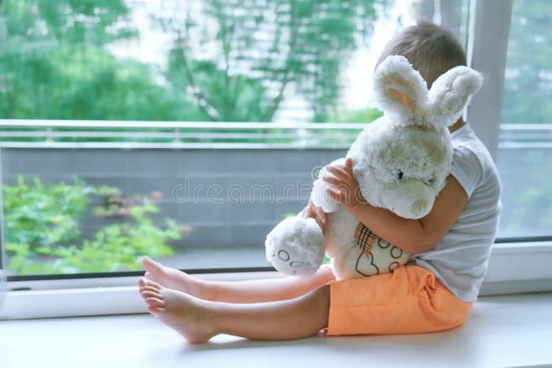Garçon de deux ans se reposant par la fenêtre et les étreintes un lapin de jouet temps pluvieux, papa de attente à venir à la mai images libres de droits