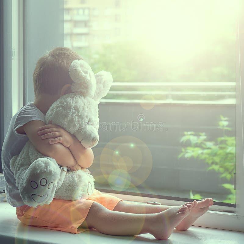 Garçon de deux ans se reposant par la fenêtre et les étreintes un lapin de jouet temps pluvieux, papa de attente à venir à la mai photographie stock libre de droits