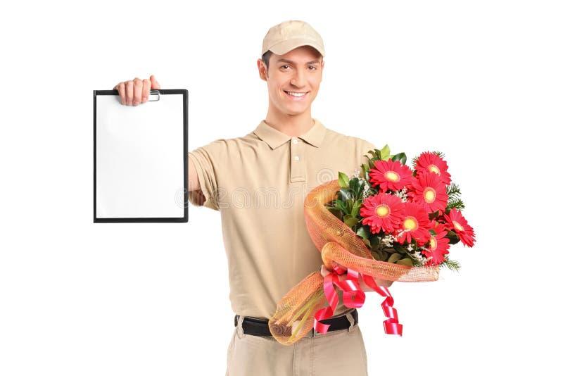 Garçon de distribution retenant un bouquet des fleurs photographie stock