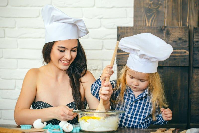 Garçon de femme et d'enfant dans des chapeaux de chef avec la cuillère images stock