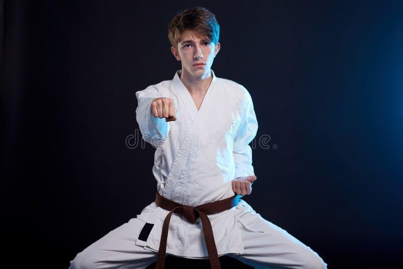 Garçon de karaté dans le kimono posant dans le studio Concept de sport photos libres de droits