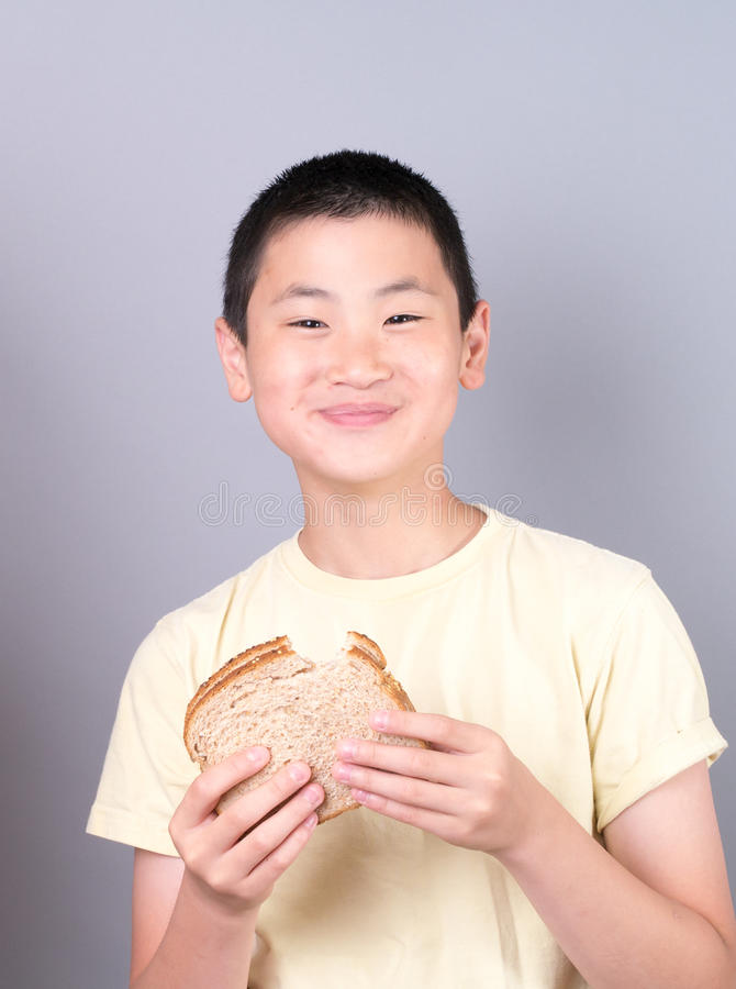 Garçon de l'adolescence asiatique mangeant un sandwich photo libre de droits