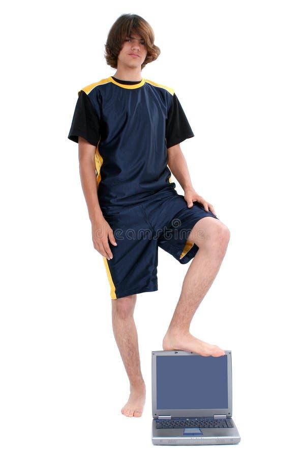 Garçon de l'adolescence aux pieds nus restant avec l'ordinateur portable au-dessus du blanc photos libres de droits