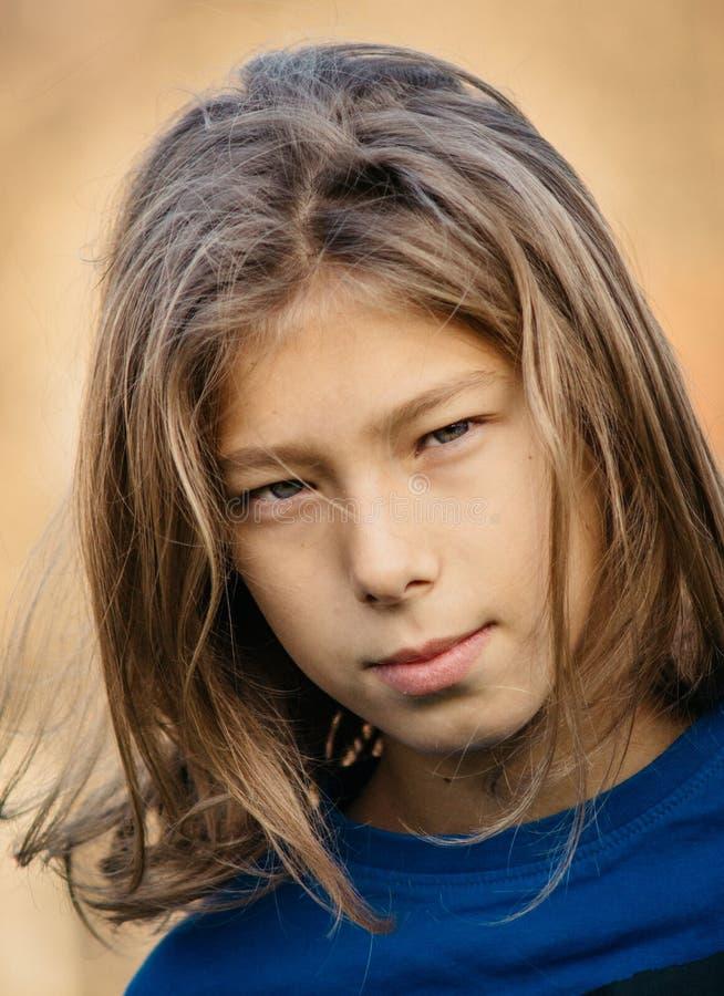 Garçon de l'adolescence avec de longs cheveux photo libre de droits