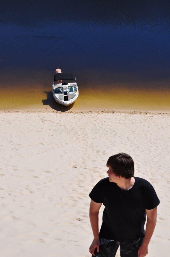 Garçon de l'adolescence avec le bateau sur la rivière photos libres de droits