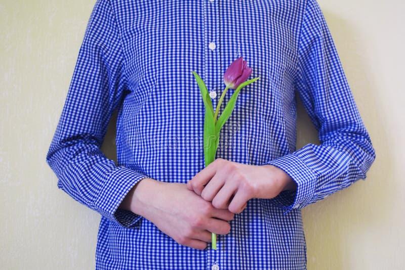 Garçon de l'adolescence avec une tulipe violette dans des mains photos libres de droits