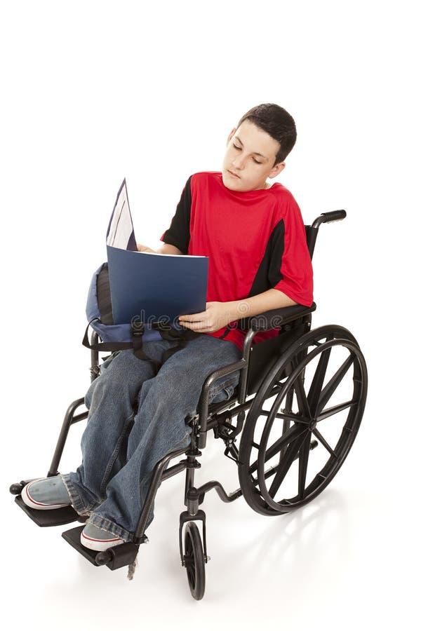 Garçon de l'adolescence dans l'étude de fauteuil roulant photos stock