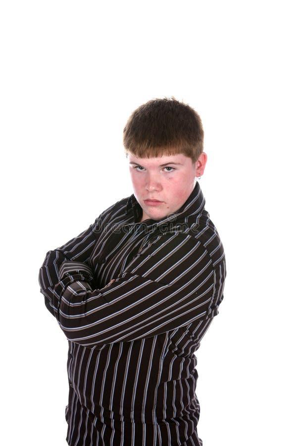 Garçon de l'adolescence dans la chemise rayée avec des bras croisés images stock